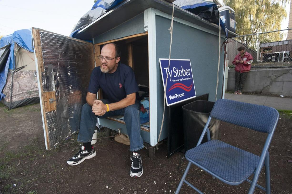 Lloyd Dodge sits in his hut Tuesday at a homeless camp near Share House in downtown Vancouver.