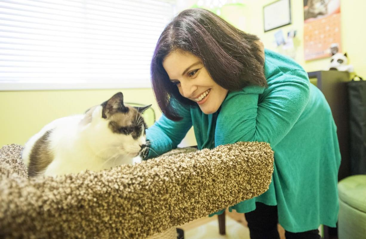 Marci Koski, a certified cat behaviorist, smiles at one of her cats at her home in Vancouver. Koski said her primary goal is to keep cats out of shelters.