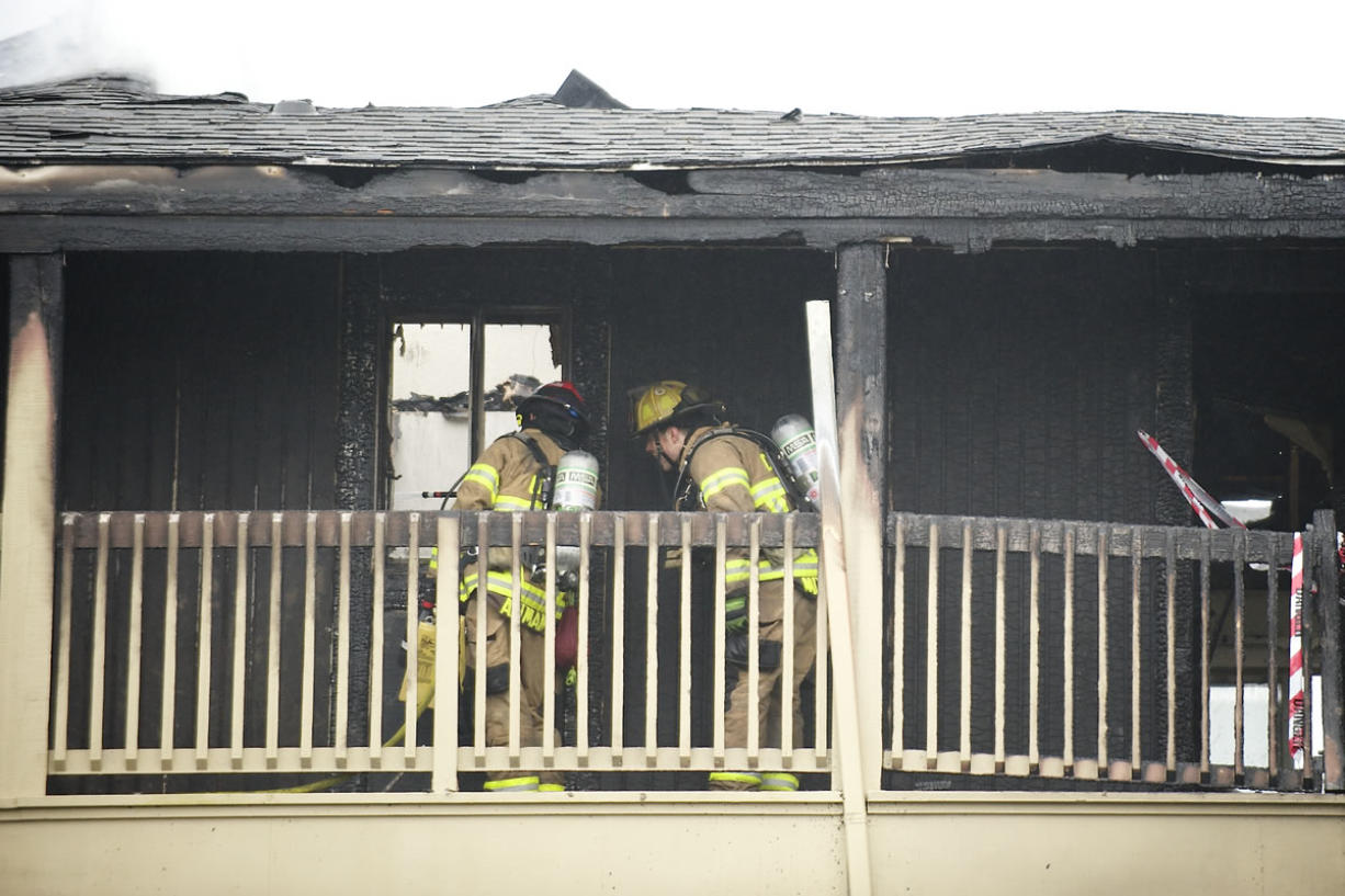 Fire fighters clean up a fire that destroyed an apartment complex at the Bridge Creek apartments Sunday March 16, 2014 in Vancouver, Washington.