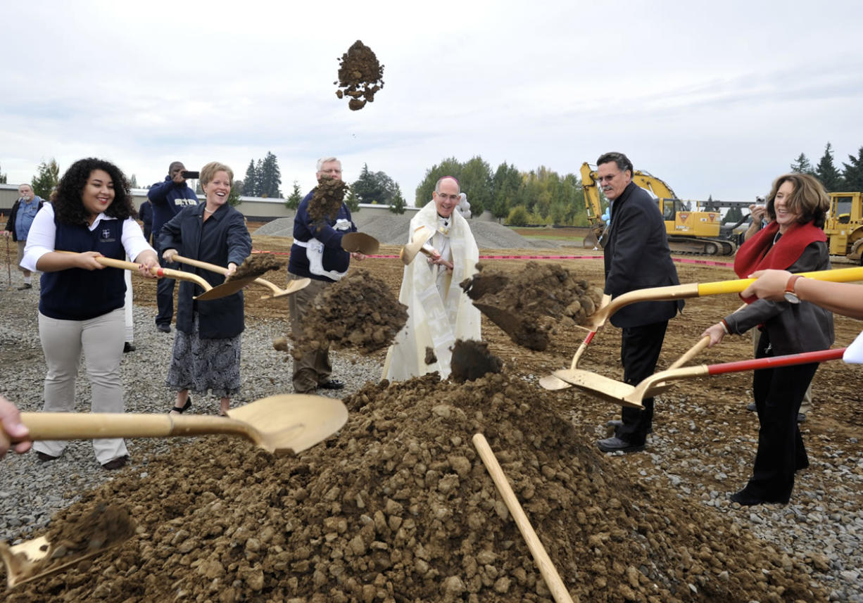 Archbishop of Seattle J. Peter Sartain, center, helps shovel dirt at a blessing and groundbreaking ceremony Saturday on the future site of Seton Catholic College Preparatory High School in Vancouver. The new building is scheduled to open for next school year in September.