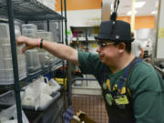 Clinton Cotton puts away dishes during his shift at the Fisher's Landing New Seasons Market.