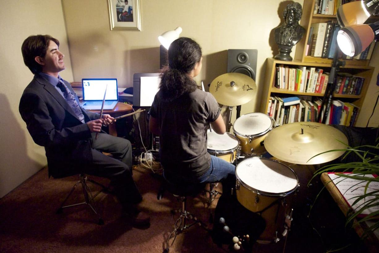 Photos by Steven Lane/The Columbian Vaughn Brown, left, a deaf-blind percussionist, teaches his student Leilani Towner, seated at the drum kit. After graduating from Washington State School for the Blind, the percussionist graduated from Berklee College of Music in Boston.