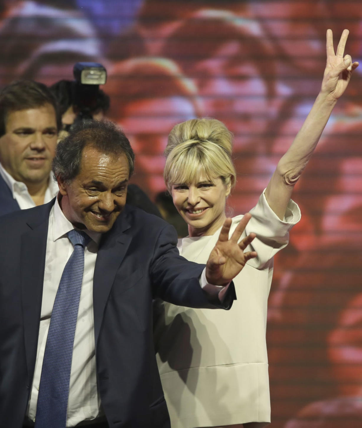 Accompanied by his wife, Karina Rabolini, Buenos Aires' Governor and ruling party presidential candidate Daniel Scioli, left, greets supporters Sunday at Luna Park in Buenos Aires, Argentina.