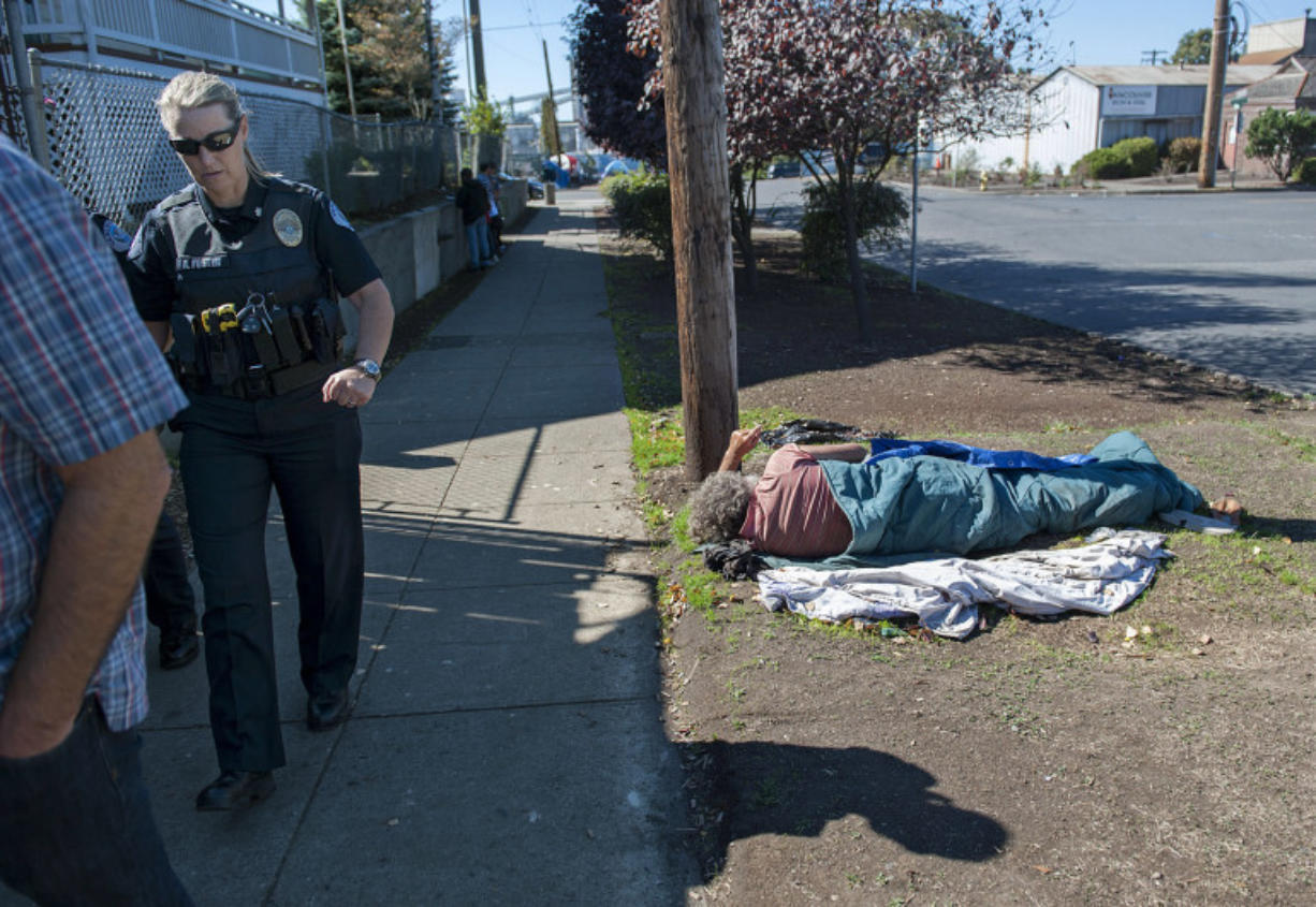 Commander Amy Foster, left, joins elected officials and others on Sept. 21 as they tour an area of downtown Vancouver facing issues with homelessness as a man sleeps on the ground nearby.