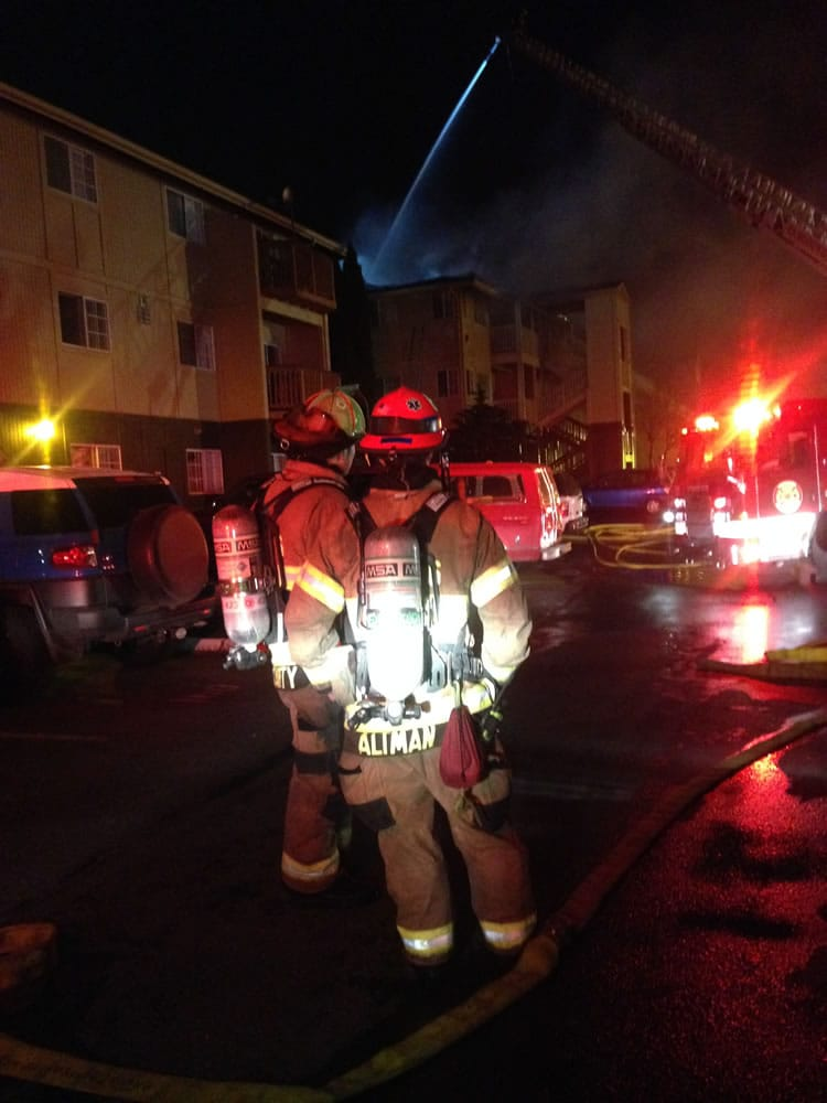 Firefighters consult as they work to contain a fire at the Bridge Creek Apartments today.