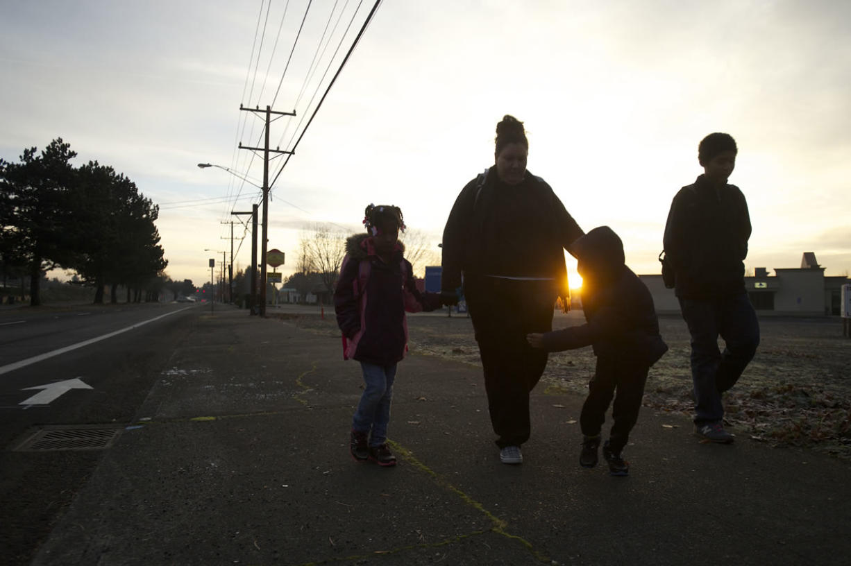Jessica Richey, second from left, and her children, Saakkaaya, 7, left; Ezekiel, 7, second from right; and Isaac, 12, make the early-morning trek to school. The family has been homeless since the beginning of the school year.