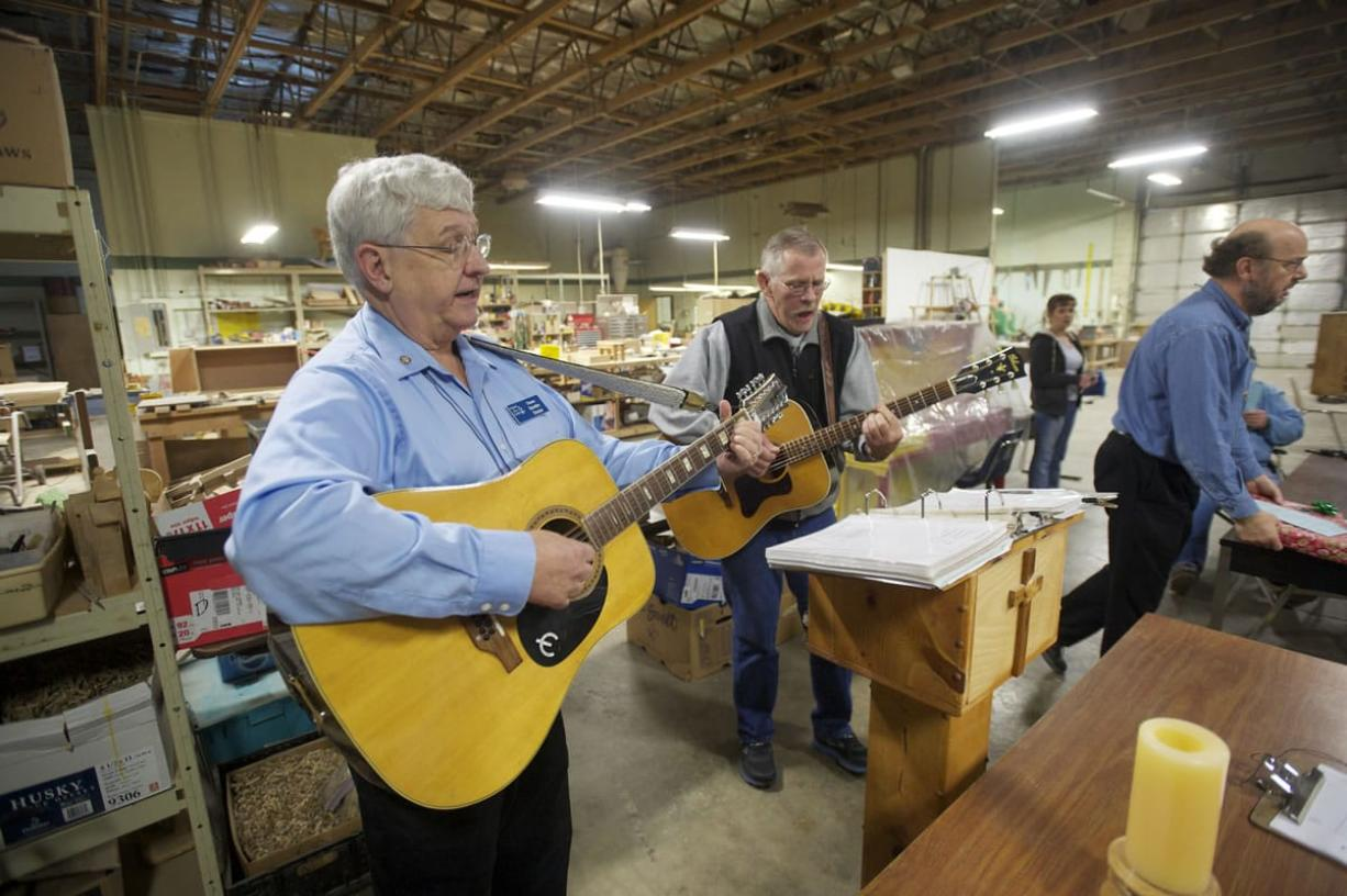 The Rev. Duane Sich, left, founder and longtime leader of homeless ministry Friends of the Carpenter, leads a musical prayer service on his 12-string guitar.