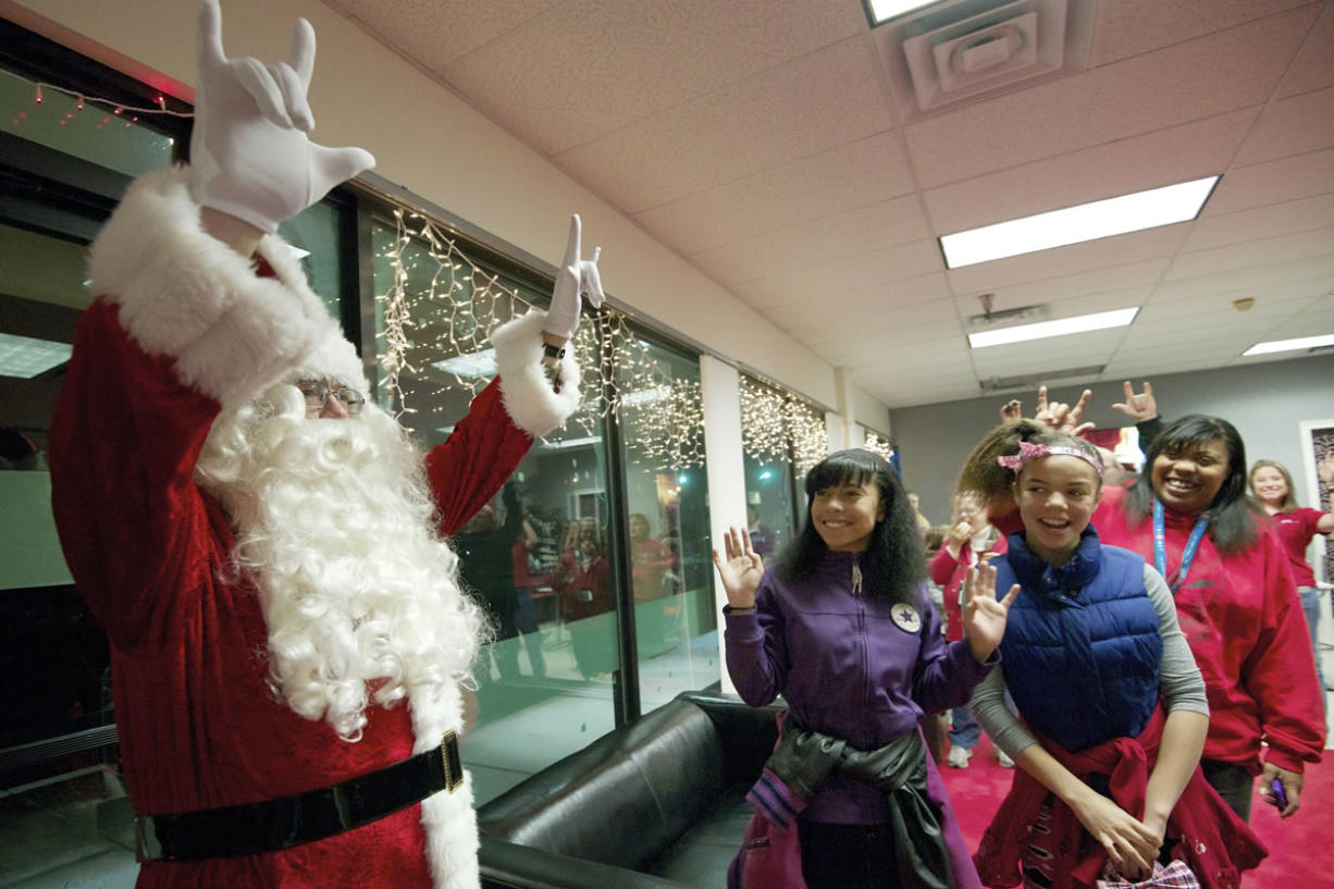 Chris Balduc, left, greets attendees using American Sign Language at a DeafVibe Foundation holiday party on Dec. 13 at their Vancouver office. Balduc is a case worker for the Southwest Washington Center of the Deaf and Hard of Hearing.