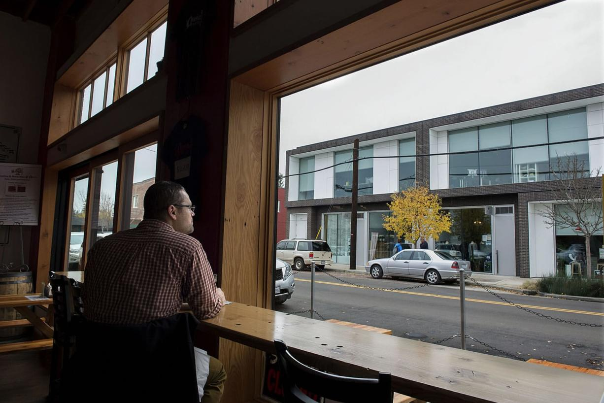 Jeremy Chitwood of Salem, Ore., checks out the view from Amnesia Brewing while enjoying lunch Thursday afternoon in up-and-coming downtown Washougal. A new downtown association is trying to build on the recent success Washougal has had in attracting new businesses and customers.