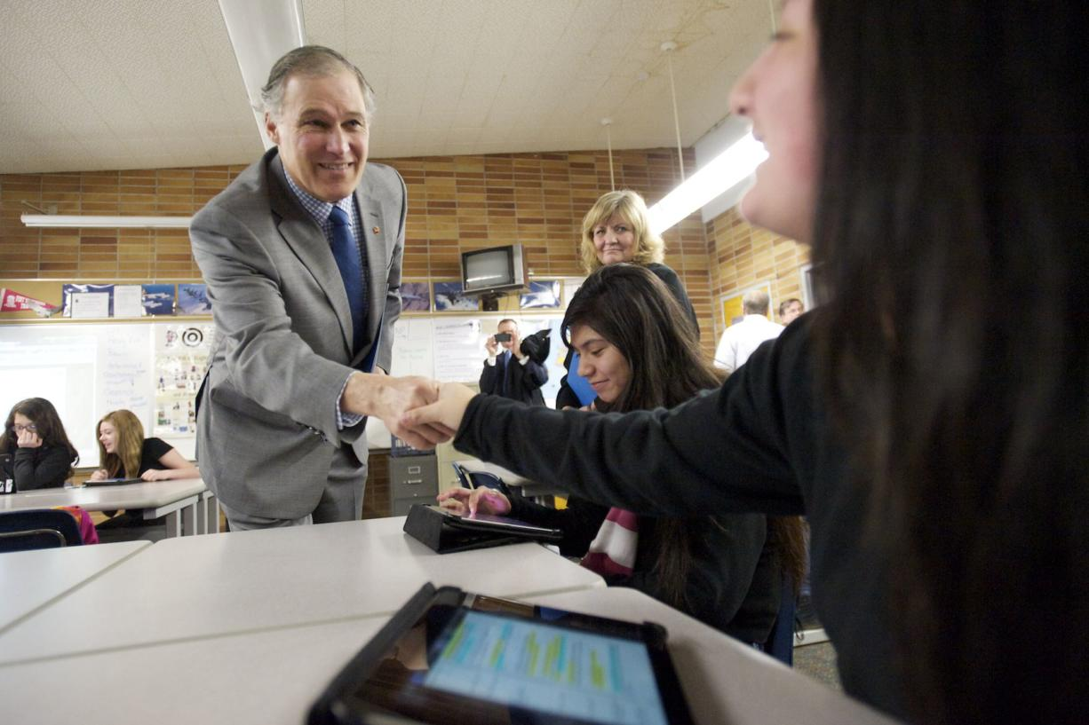 Gov. Jay Inslee, left, and his wife, Trudi, greet McLoughlin Middle School students Lizbeth Martinez, seated at center, and Karol Hoyos, both 14, in Bill Sixour's U.S. history class on Wednesday. They were using tablets to learn about the Underground Railroad. The Inslees visited two classes to observe how students and teachers use tablets at school.