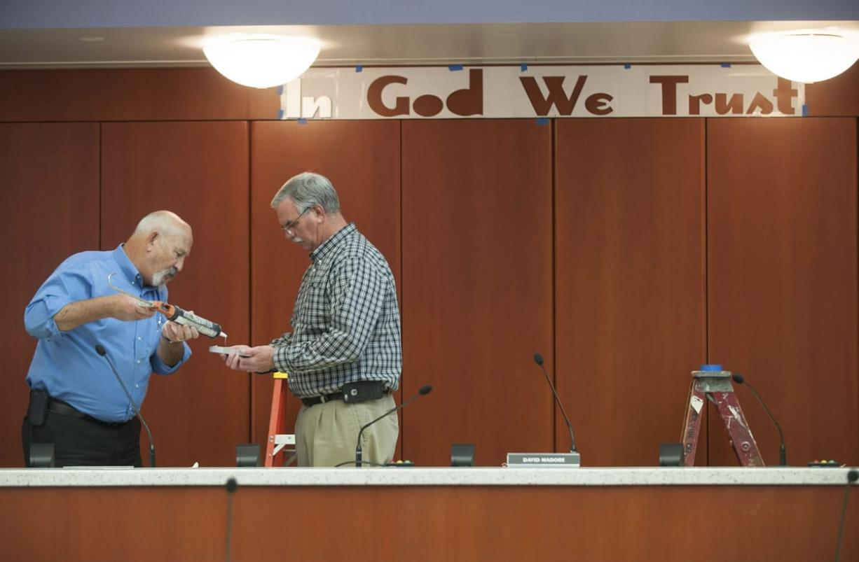 "County facilities managers Darrel Stump, left and Mike Wright put glue on the back of a letter as the ""In God We Trust "" slogan is installed Thursday. (Natalie Behring/The Columbian)"