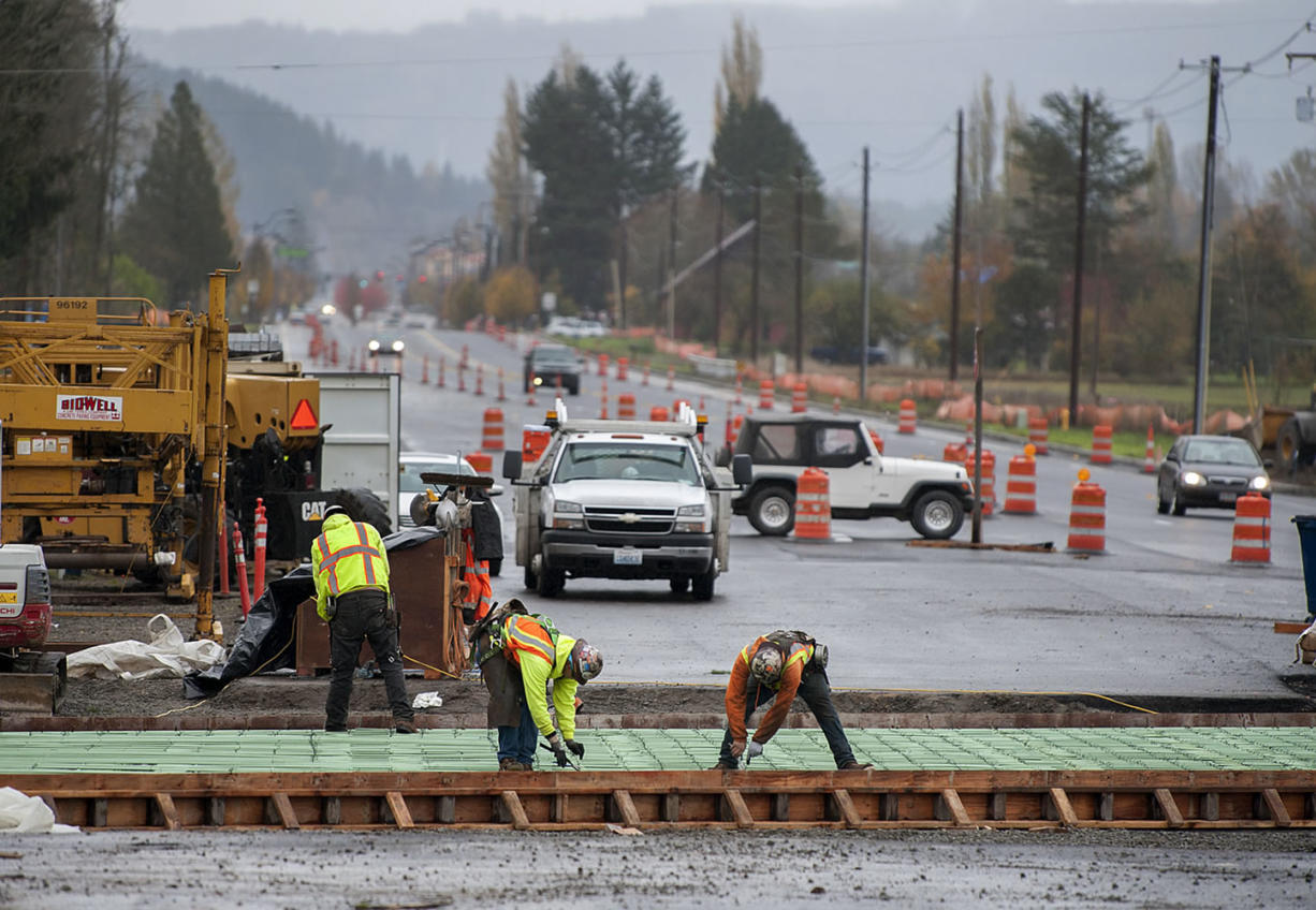 Motorists navigate around construction crews Monday as they continue work to widen state Highway 502 between Interstate 5 and Battle Ground.