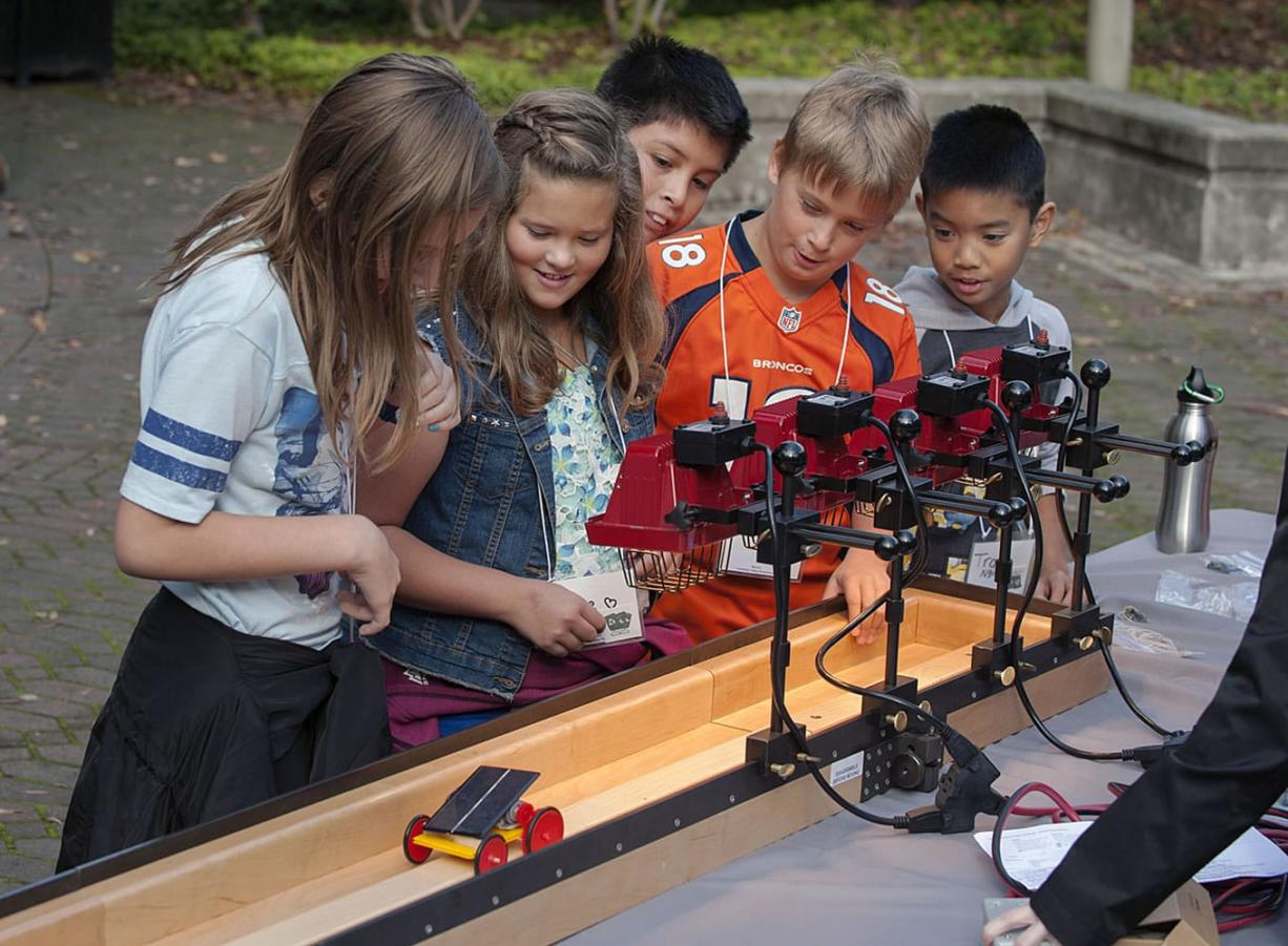 Columbia Valley Elementary School fourth-graders Lily Scholl, from left, Paige Holstad, Victor Jimenez, Payton Holstad and Travis Nguyen take their solar-powered car for a test run Tuesday at the Water Resources Education Center. (Amanda Cowan/The Columbian)