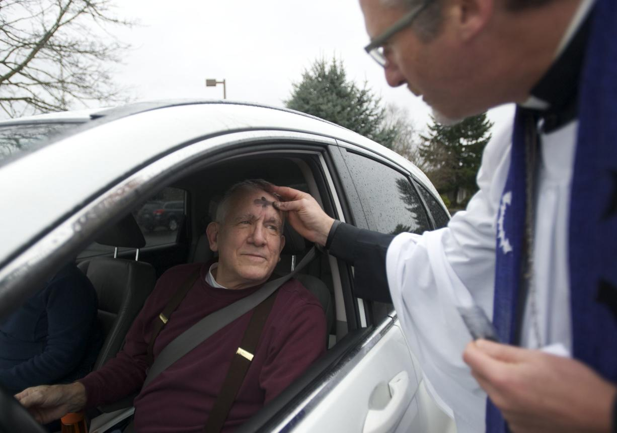 The Rev. Tom Warne provides a drive-up anointing of ashes to Gary Hatzenbeler on Wednesday outside of the Church of the Good Shepherd.