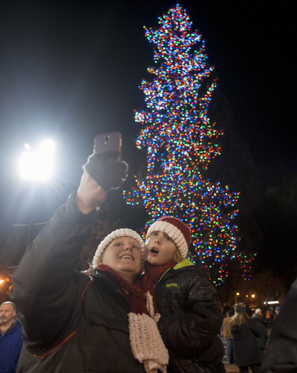 Beka Schueth and son Nathanael take a selfie as they attend the annual Christmas tree lighting event at Esther Short Park on Friday night.