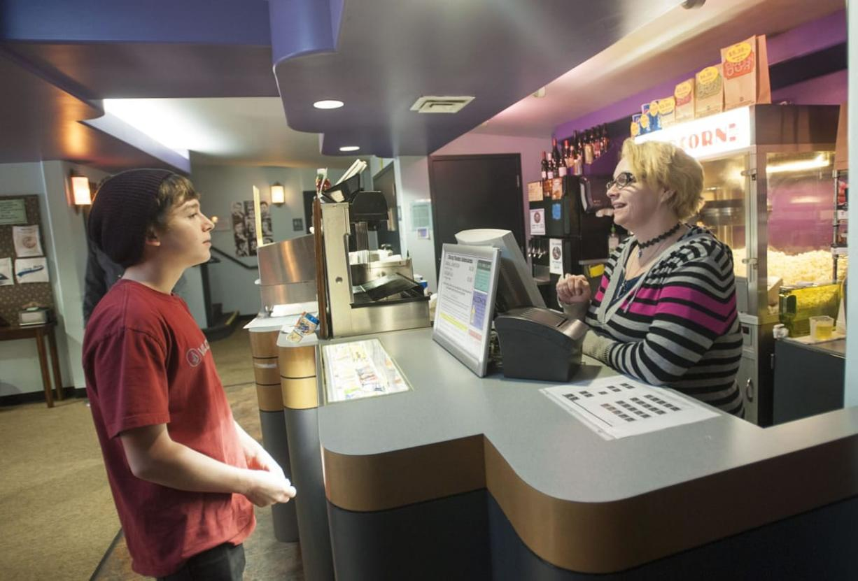 Liberty Theatre employee Angel Brueker sells a movie ticket to Tyler Drake, 15, on a recent Saturday. The Liberty is working to market its offerings to younger moviegoers as part of its effort to attract new audiences.