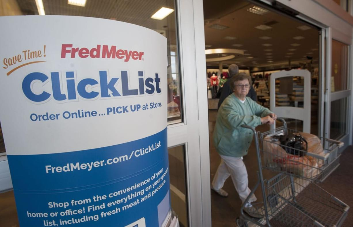 Signs welcome shoppers to participate in online grocery shopping at the Fred Meyer store in Orchards.