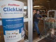 A shopper pushes a grocery cart past a sign welcoming shoppers to participate in online grocery shopping at Fred Meyers in Vancouver Tuesday November 3 , 2015.(Natalie Behring/The Columbian) A shopper pushes a grocery cart past a sign welcoming shoppers to participate in online grocery shopping at Fred Meyers in Vancouver Tuesday November 3 , 2015.(Natalie Behring/The Columbian) The Fred Meyer store in Orchards at 7411 N.E. 117th Ave. is the first in the chain to offer an online grocery service. Customers can order online, set a pickup time for the next day, and do their grocery shopping without setting foot in the store. (Natalie Behring/The Columbian)