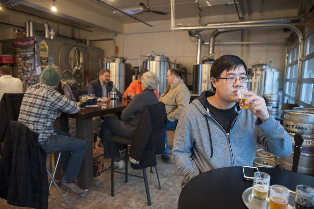 Kevin Fujii of Davis, Calif., enjoys beer with the Friday evening crowd at Mt. Tabor Brewing's taproom at 113 W. Ninth St. in Vancouver.  With Mt. Tabor's construction of a new restaurant in Felida and a production facility in Portland, the downtown taproom and brewery will close in June.
