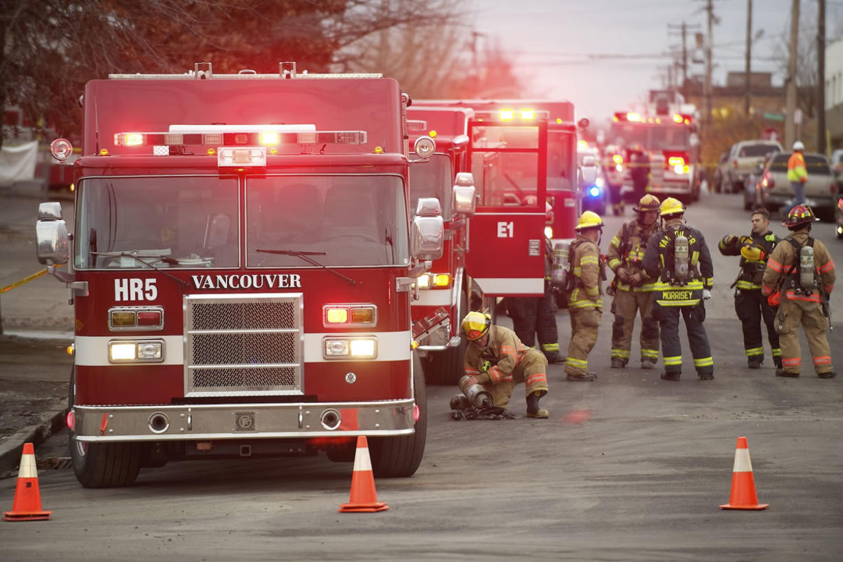 Firefighters with the Vancouver Fire Department stand by to investigate after a floor collapsed at Vancouver Warehouse and Distribution Co., 1101 W.