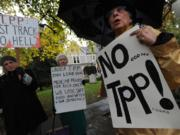 Dorethea Simone, right, and others protest against the Trans Pacific Partnership along Fort Vancouver Way in Vancouver on Thursday.