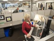 Business services consultant Marnie Farness gets settled into WorkSource's new offices, 204 S.E. Stone Mill Drive, on Monday.