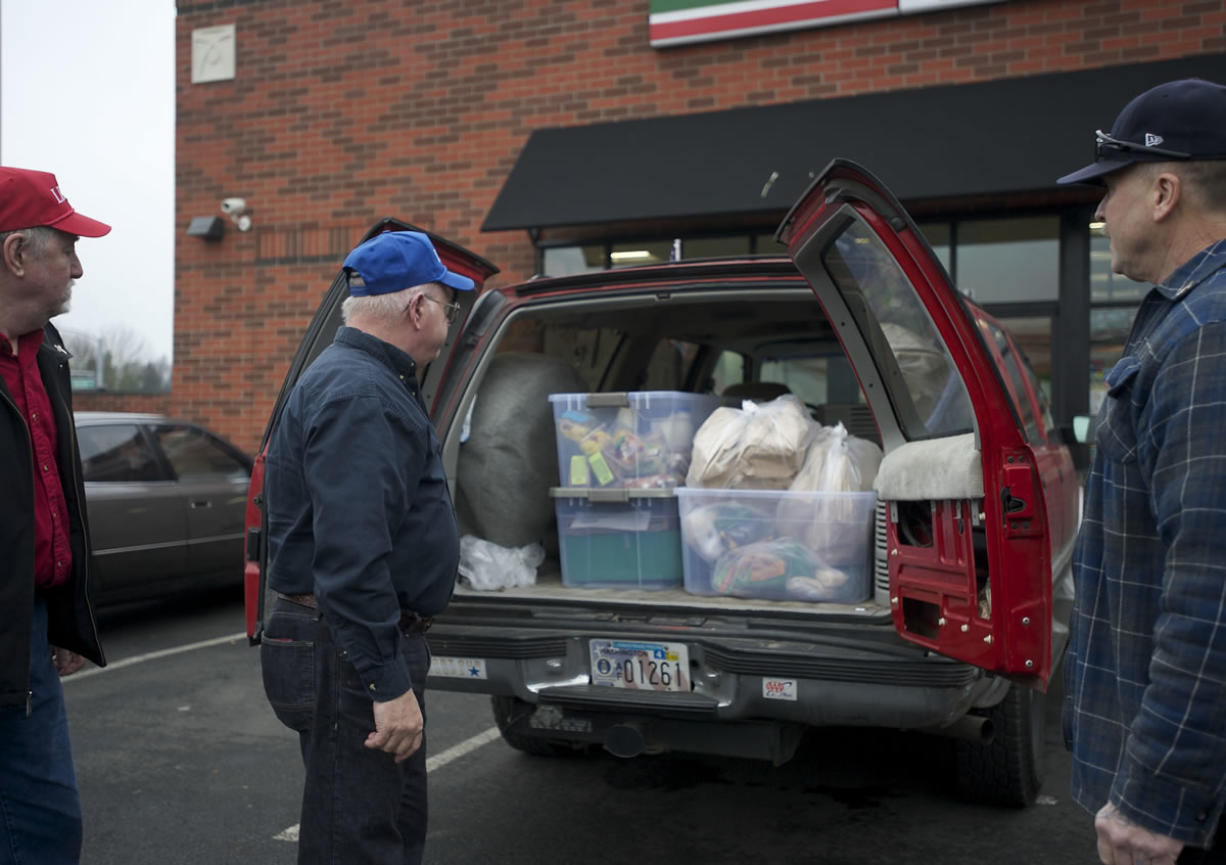George Golden, center, director of LINKS, Michael Rankin, left, and Don Meuchel pick up perishable food items at a 7-Eleven in Vancouver on Friday.