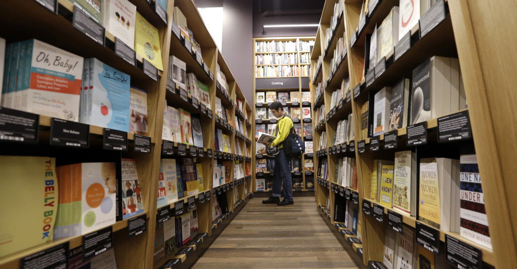 A customer shops at the opening day for Amazon Books, the first brick-and-mortar retail store for online retail giant Amazon, Tuesday, Nov. 3, 2015, in Seattle. The company says the Seattle store, coming two decades after it began selling books over the Internet, will be a physical extension of its website, combining the benefits of online and traditional book shopping. Prices at the store will be the same as books sold online.