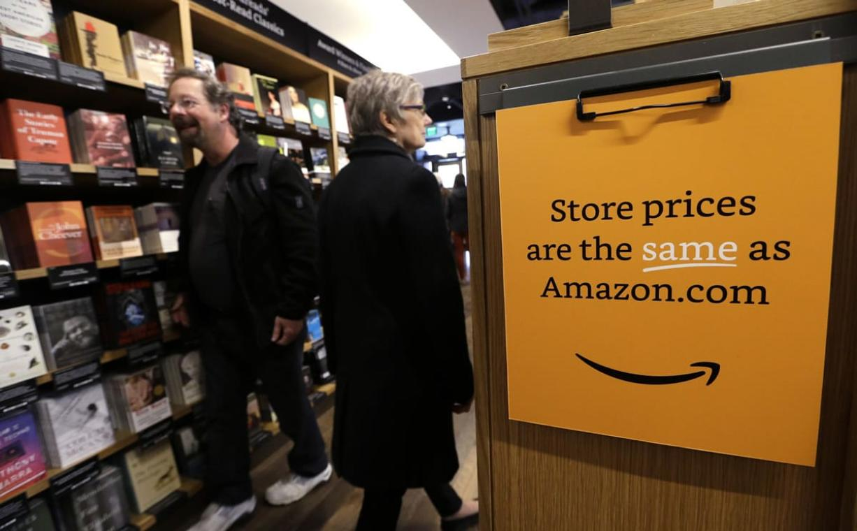 Customers shop on the opening day for Amazon Books, the first brick-and-mortar retail store for online retail giant Amazon, on Tuesday in Seattle.