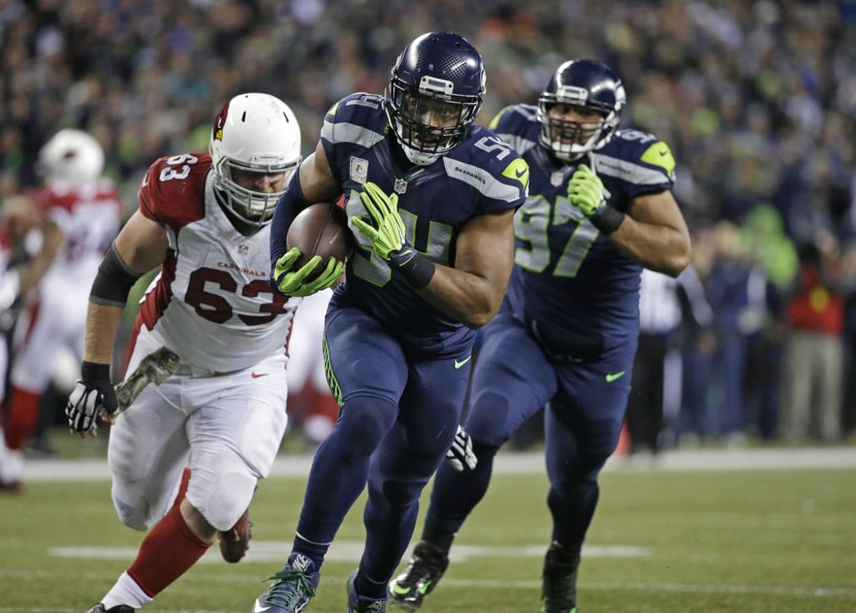 Seattle Seahawks middle linebacker Bobby Wagner (54) returns an Arizona Cardinals fumble for a touchdown as Cardinals' Lyle Sendlein (63) pursues during the second half of an NFL football game, Sunday, Nov. 15, 2015, in Seattle.