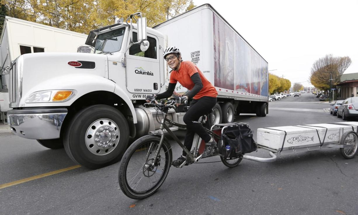 Heidi Lappetito pedals her cargo bike past a parked beer truck as she hauls a trailer loaded with frozen salmon in Port Townsend.