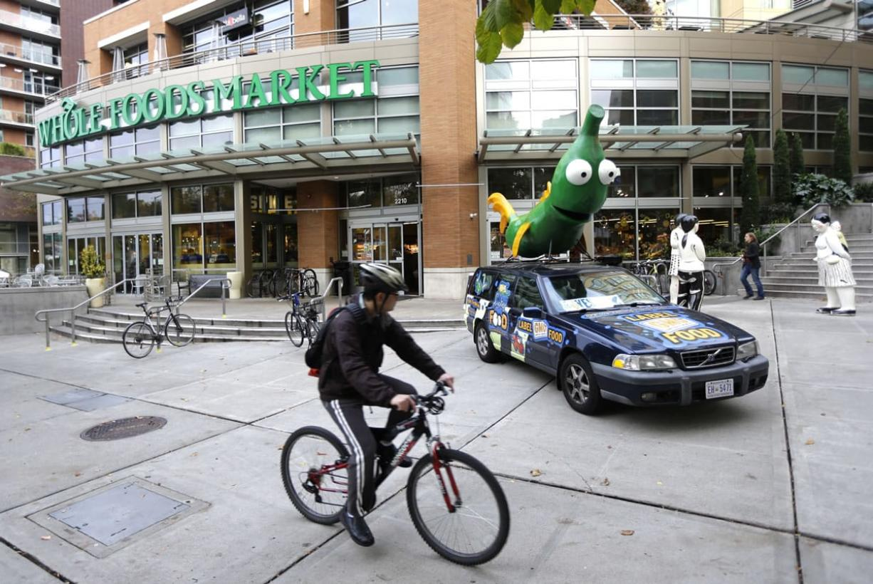 A cyclist rides past a car with a figure of a soybean crossed with a fish on top of of it Tuesday.