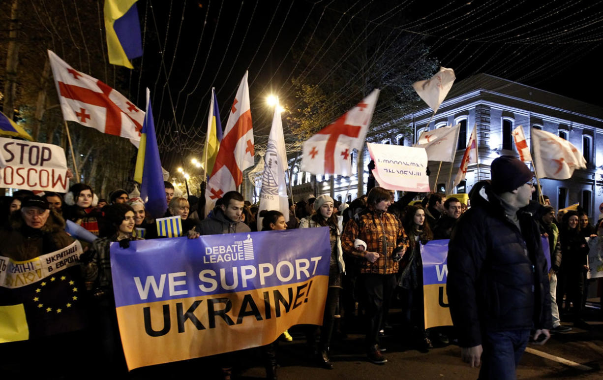 Demonstrators carry posters and Georgian and Ukrainian flags as they head to a rally in support of the Ukrainian opposition in downtown Tbilisi, Georgia, on Wednesday.