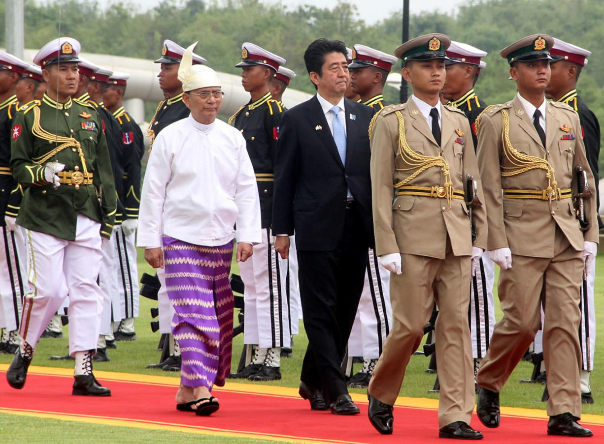 Japanese Prime Minister Shinzo Abe, center right, and Myanmar President Thein Sein, center left, inspect the honor guard at Presidential Palace on Sunday in Naypyitaw, Myanmar.