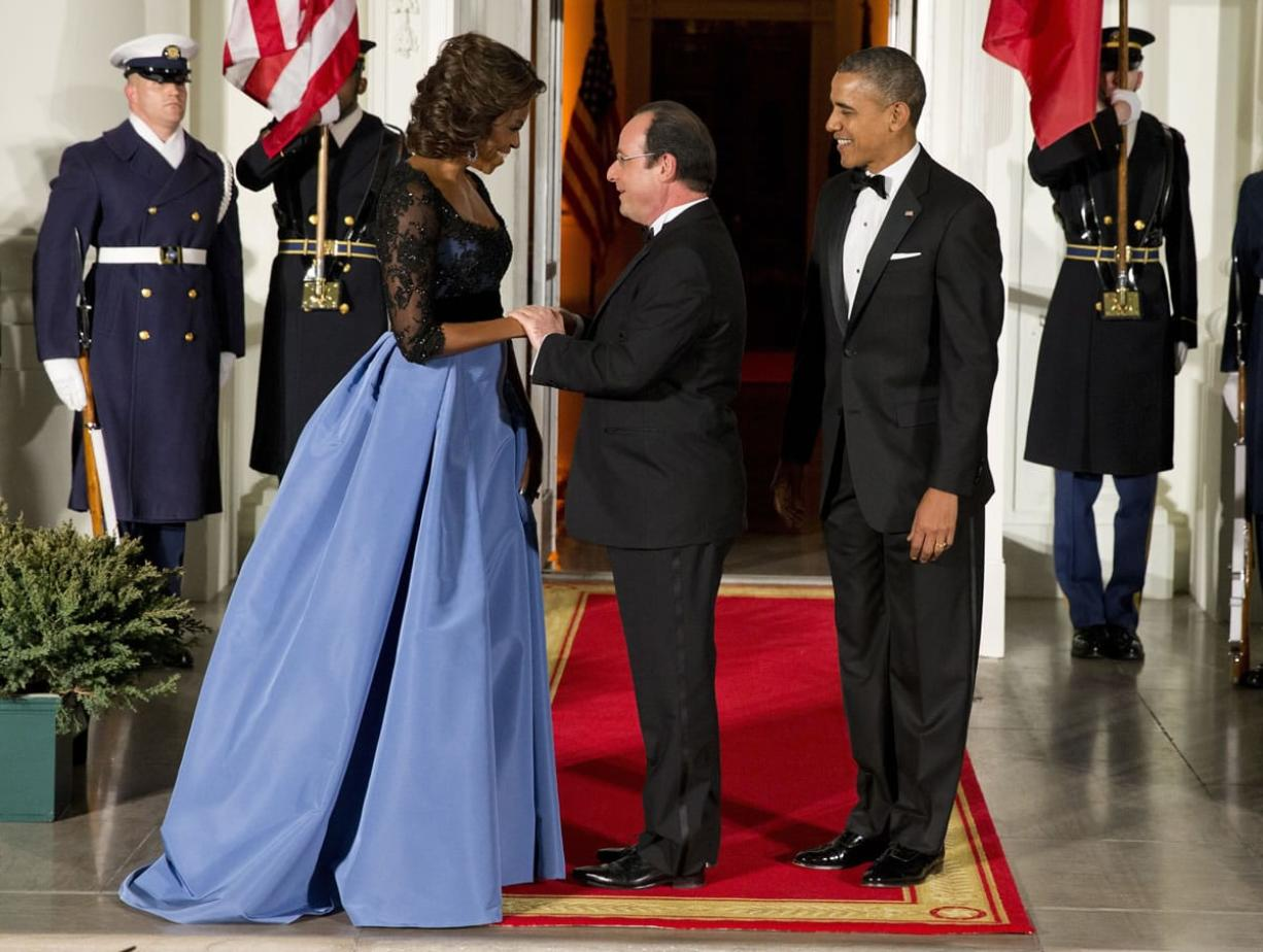 First lady Michelle Obama and President Barack Obama welcome French President Francois Hollande, center, to a state dinner at the White House on Tuesday.