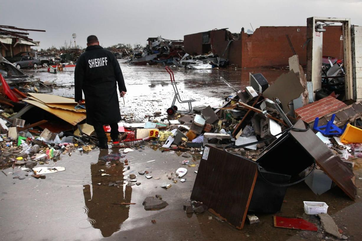 A deputy sheriff walks through the rubble at Plaza Towers Elementary School in Moore, Okla., on May 22.