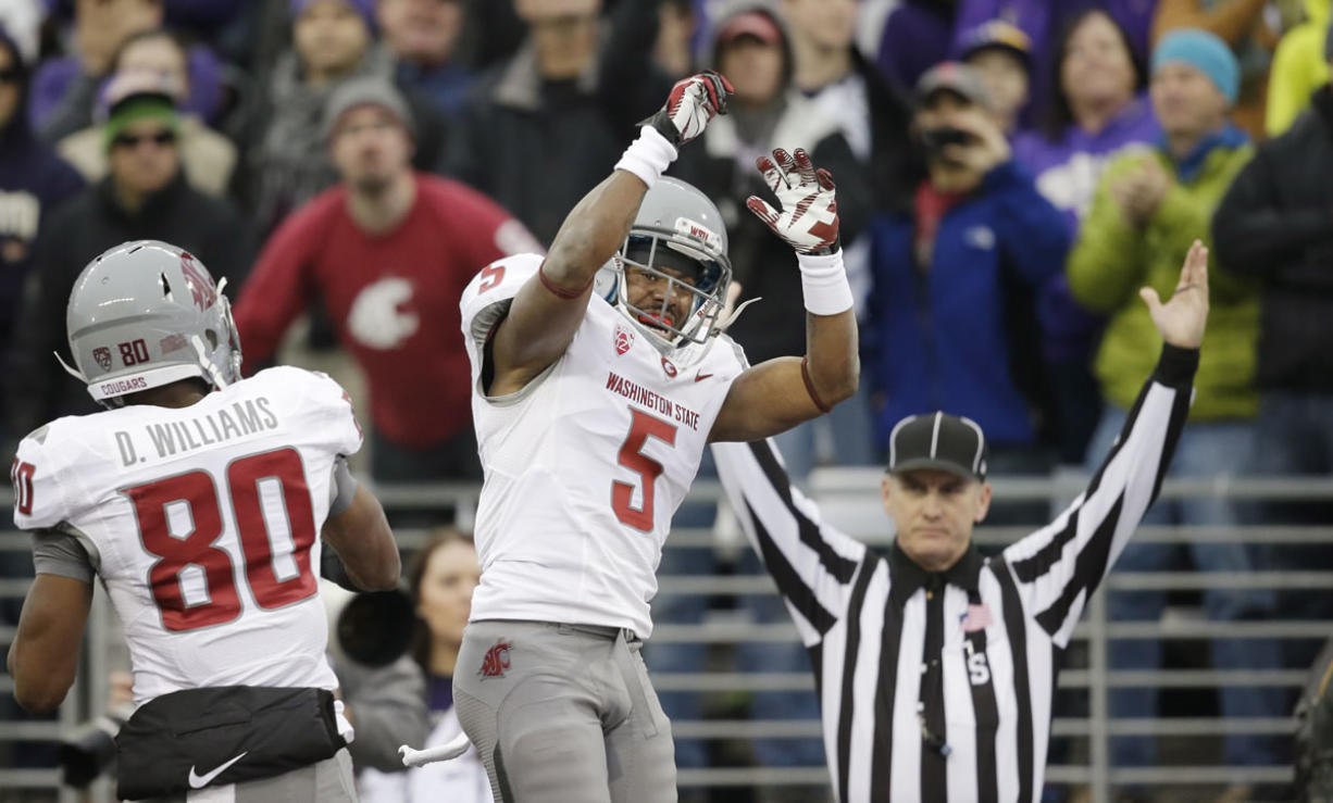 Washington State's Rickey Galvin (5) celebrates his 14-yard touchdown reception with Dom Williams as official Bernie Hulscher signals the score in the first half Friday.