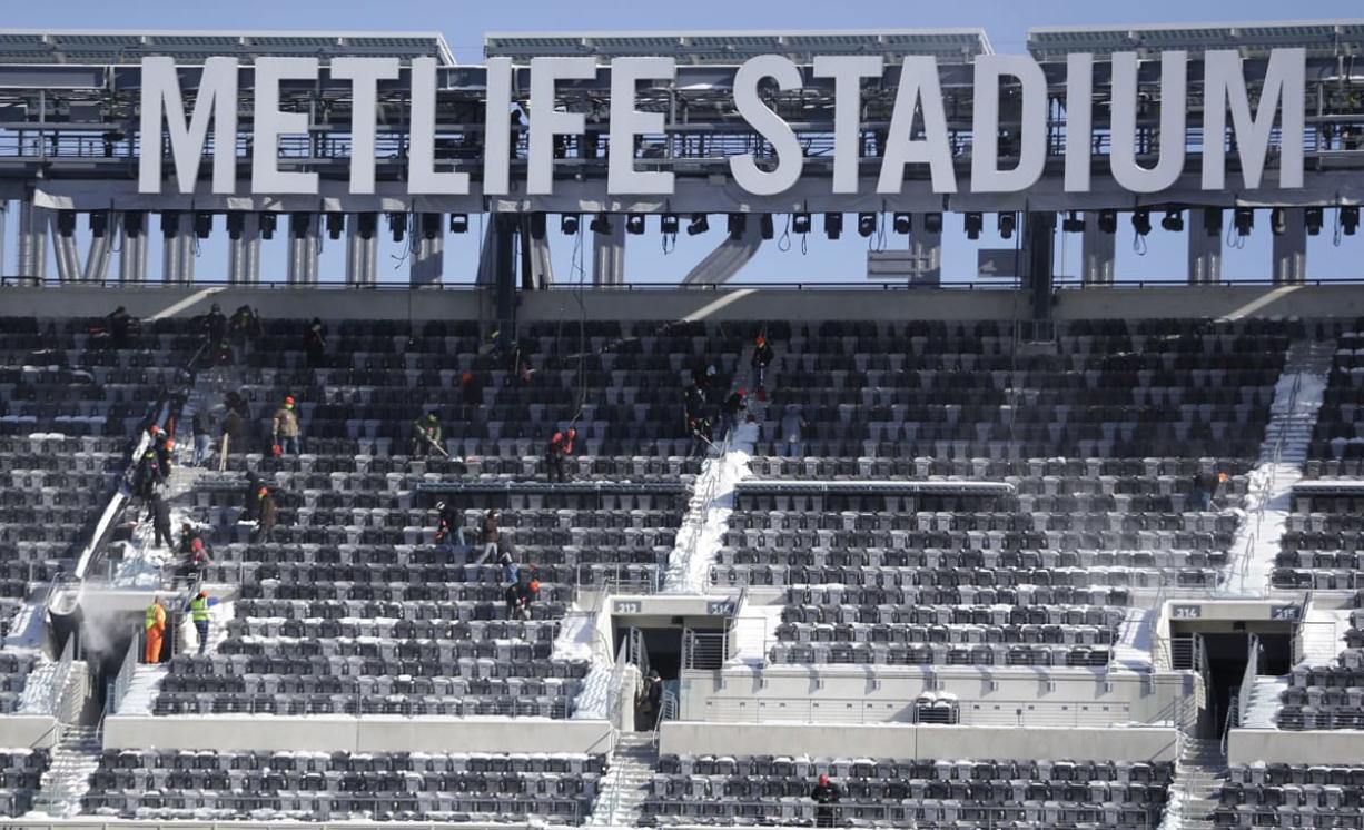 Workers shovel snow off the seats at MetLife Stadium as crews removed snow ahead of Super Bowl XLVIII following a snow storm on Wednesday in East Rutherford, N.J.