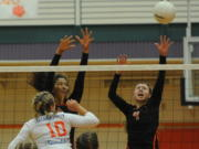 """Battle Ground High School's """"Lady Tigers"""" Ashley Watkins (C) and Kimberly Lasley (R) defend the net against Ridgefield's Madi Harter (L) at a volleyball in Battle Ground Thursday September 10, 2015."""
