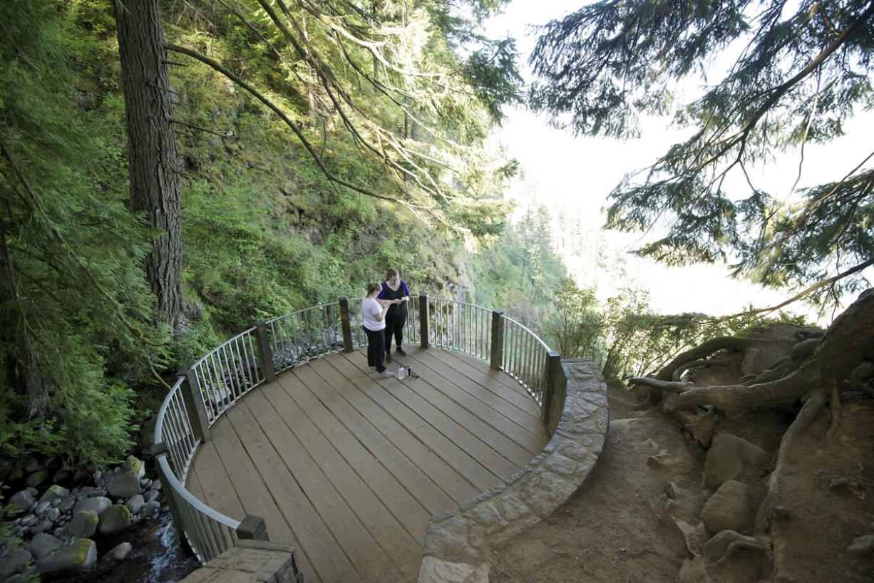 Women take photos at the top of the Multnomah Falls trail in the Columbia River Gorge.