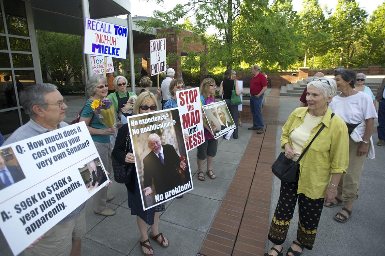 Protesters opposed to the hiring of State Sen. Don Benton stand outside the Clark County Public Services Center on Tuesday.