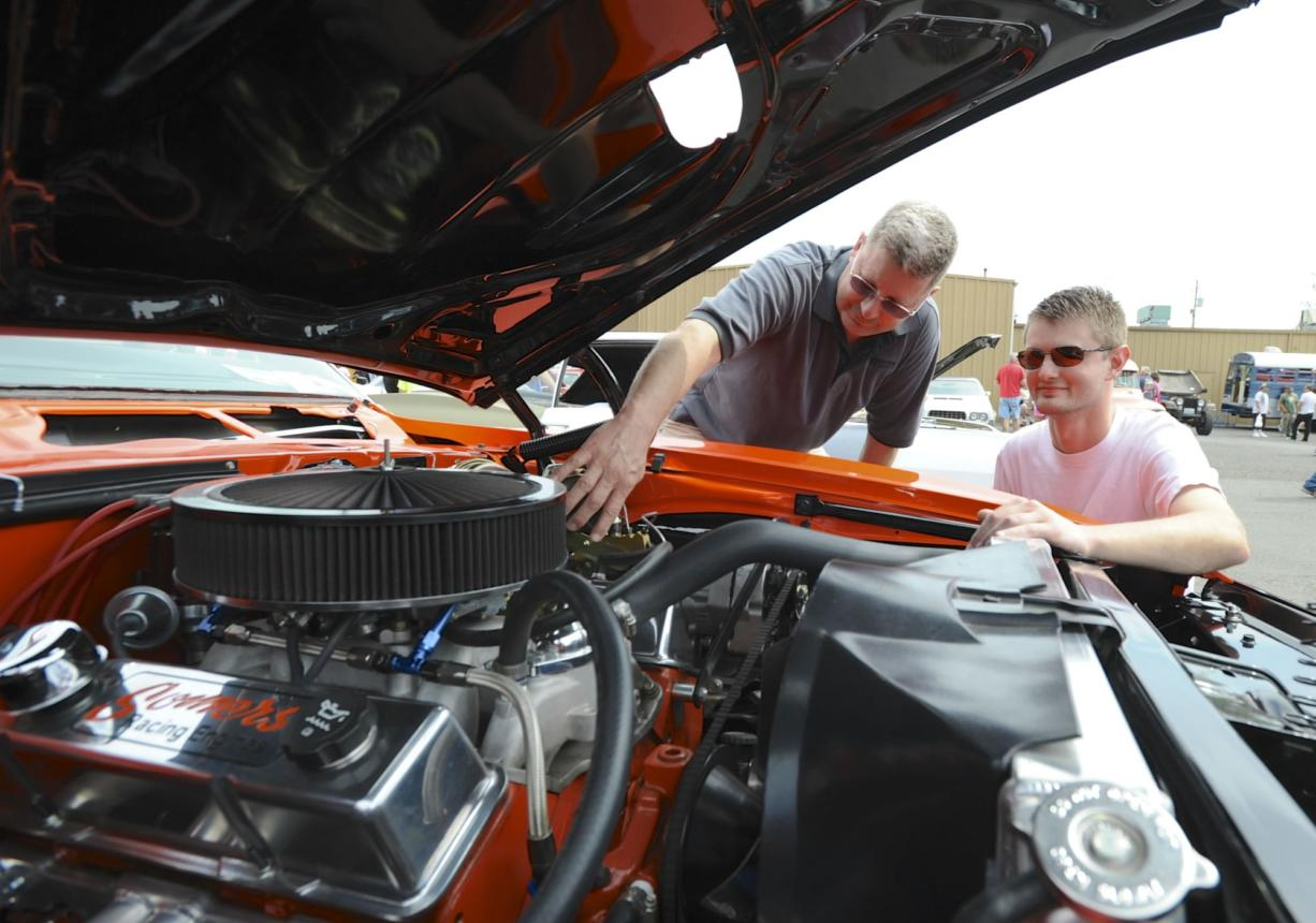 Car lovers, including Roy Rhine and son Trevor with his '68 Pontiac Firebird, gather Sunday at Pied Piper Pizza in Orchards for the annual Father's Day Cruise-in to benefit the Relay for Life cancer effort.