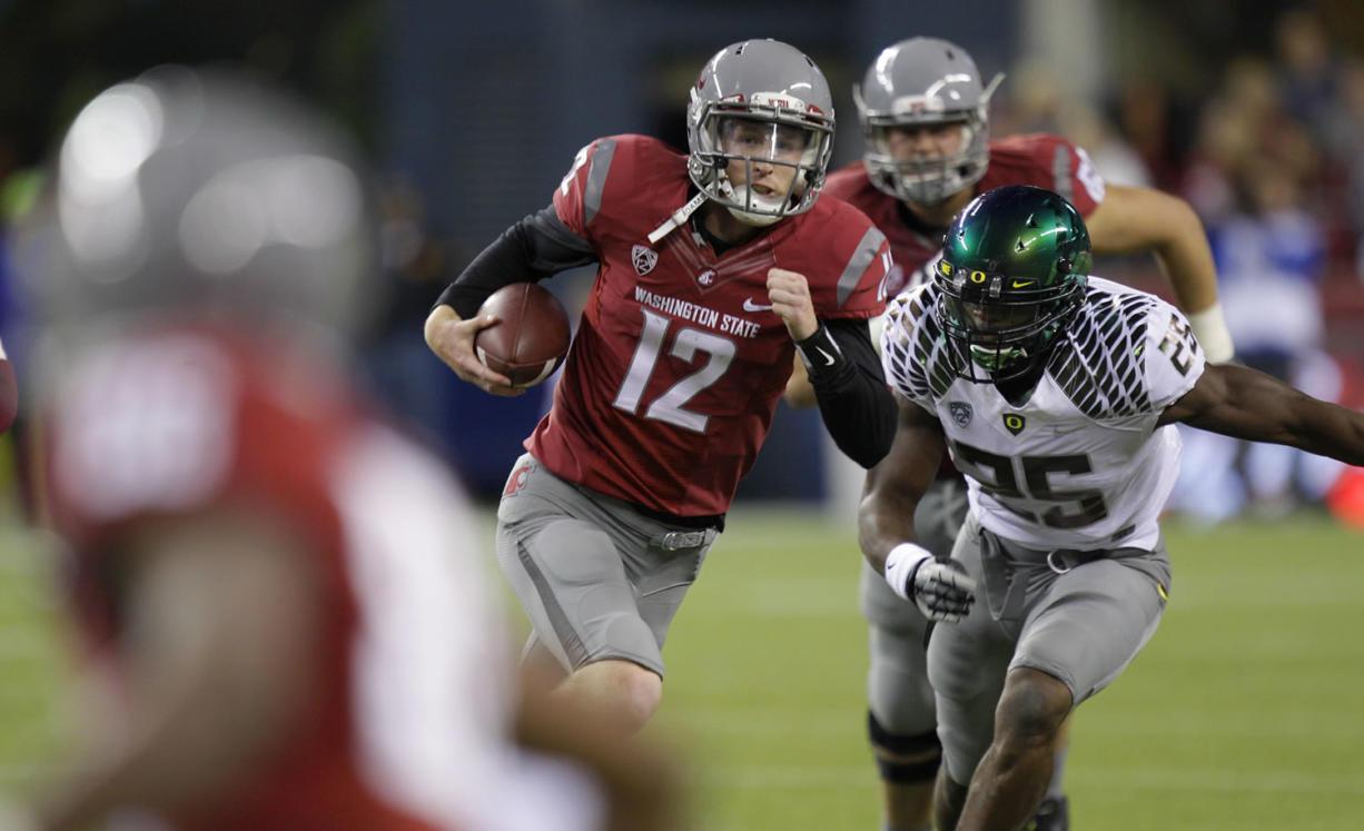 Washington State quarterback Connor Halliday scrambles with the ball as Oregon's Boseko Lokombo pursues in the second half of a game last season.