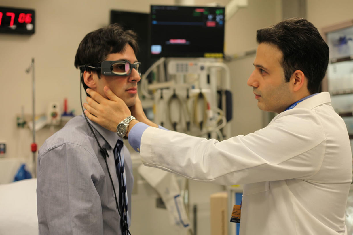 Johns Hopkins physicians Georglos Mantokoudis, left, and Ali Tehrani demonstrate the use of eye-tracking goggles that may replace expensive scans to determine if a person's dizziness is caused by an inner-ear infection or a stroke.