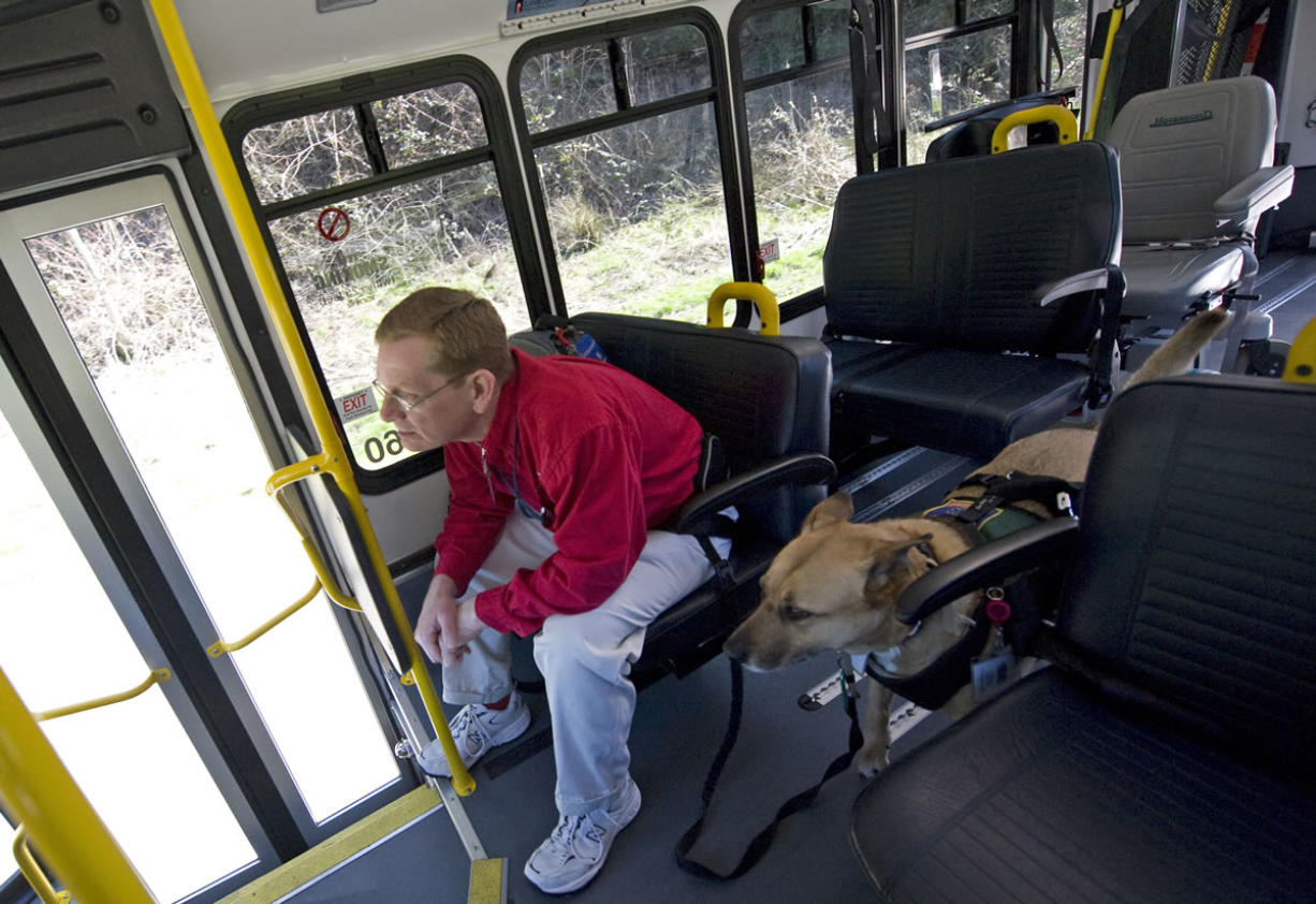 Harry Kiick of Vancouver rides a C-Van bus with his service dog, Sasha, in 2009. Kiick and Sasha have been regular C-Tran riders for the past 11 years; Sasha wears a vest and badge identifying her as a service animal.