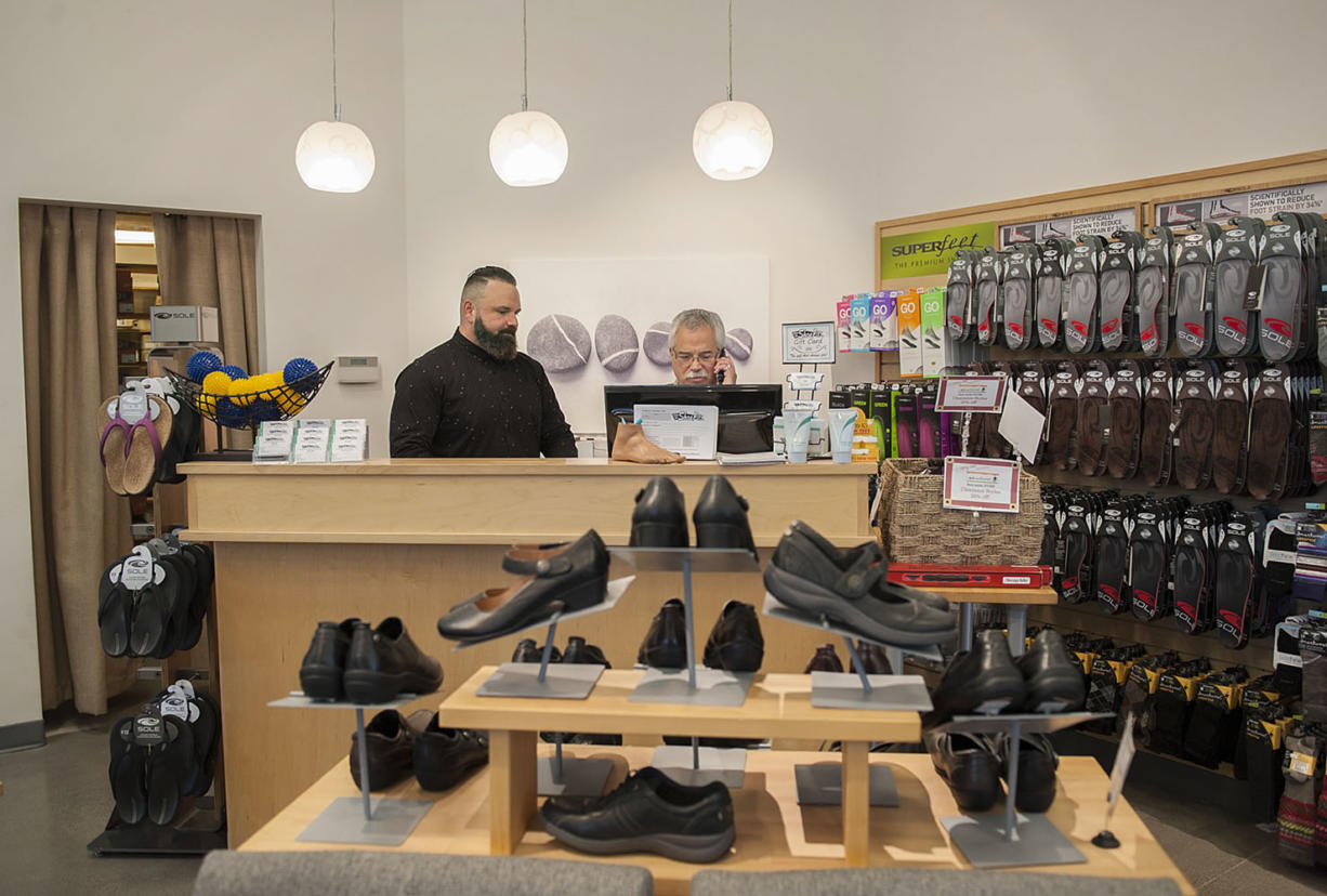 Ryan Downey, left, works behind the front counter with Jeff Horowitz on Tuesday morning at When the Shoe Fits in Southeast Vancouver.