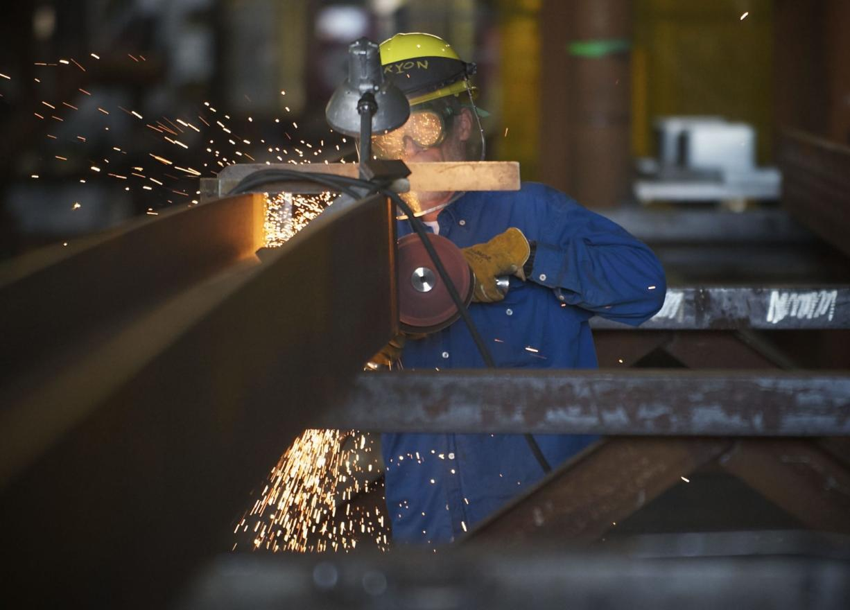 A worker uses a grinder inside Thompson Metal Fab, one of three Vancouver manufacturers that said the proposed bridge's lower height would have had a negative impact on their businesses.