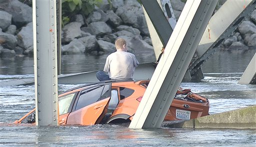 An unidentified man waits on his submerged vehicle in the Skagit River Thursday May 23, 2012. The Interstate 5 bridge over the Skagit river collapsed north of Seattle Thursday evening, dumping two vehicles into the water and sparking a rescue effort by boats and divers as three injured people were pulled from the chilly waterway.