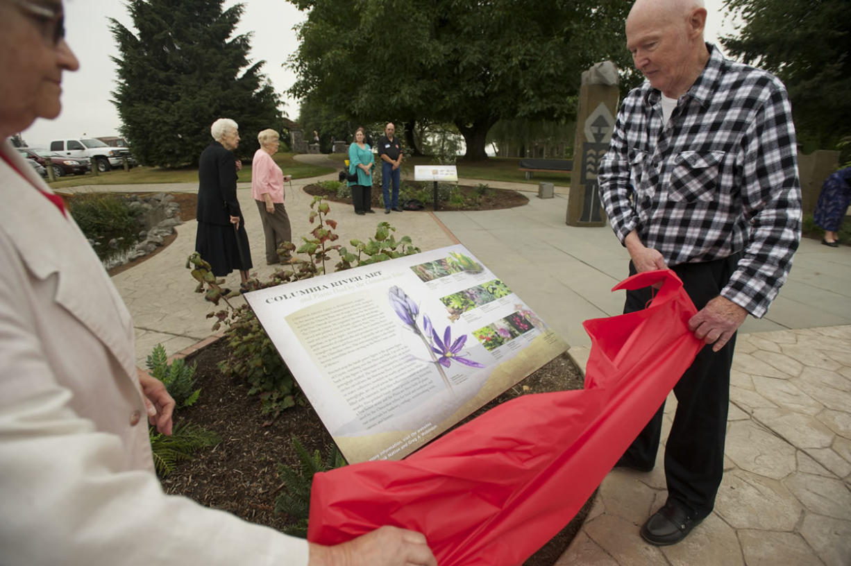 Ginny Frosh and Ted Durgan unveil one of three new interpretive panels honoring the Chinookan people Thursday at the Parkersville National Historic Site. The panels are in Chinook Plaza, at the Port of Camas-Washougal.