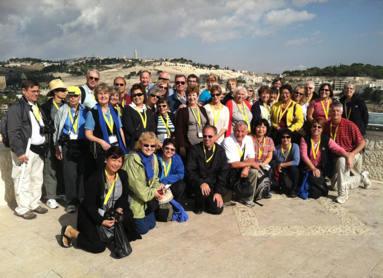 This picture of parishioners from Our Lady of Lourdes Catholic Church was taken before hostilities broke out. The group was in Jerusalem just finishing up a 12-day tour of Israel; that's the Mount of Olives behind them. Front row middle is Rev. Michael Radermacher, and Sue McDonald is far right in black vest and salmon shirt.